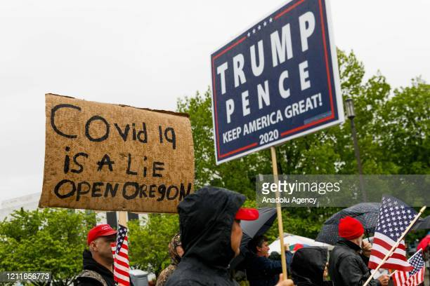 A demonstrator holds a sign reading COVID19 is a lie Open Oregon during the protest at the State Capitol in Salem Oregon United States on May 2 2020...