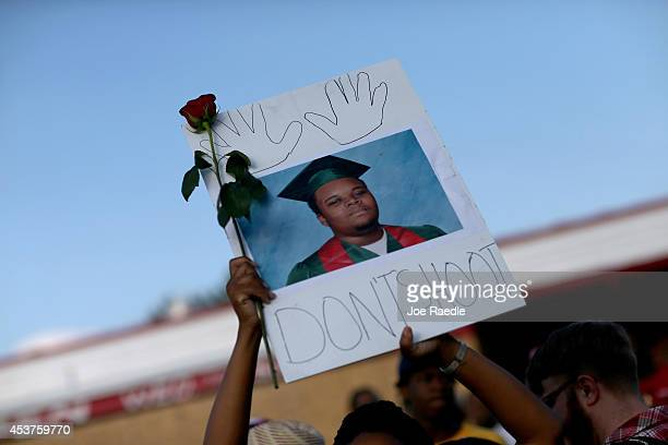"""Demonstrator holds a sign reading, """"Dont Shoot"""", with a picture of Michael Brown on August 17, 2014 in Ferguson, Missouri. Violent outbreaks have..."""