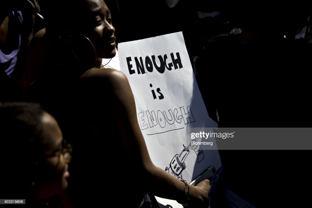 A demonstrator holds a sign reading 'Enough is Enough' while protesting gun violence outside the White House in Washington, D.C., U.S., on Wednesday, Feb. 21, 2018. President Donald Trump is meeting with students, parents and teachers who have lived through mass shooting incidents, including some from the Florida high school where last weeks mass shooting killed 17 people. Photographer: Andrew Harrer/Bloomberg via Getty Images