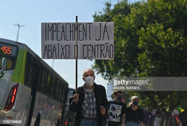 Demonstrator holds a sign reading 'impeachment now' during a protest against Brazilian President Jair Bolsonaro's handling of the COVID-19 pandemic...