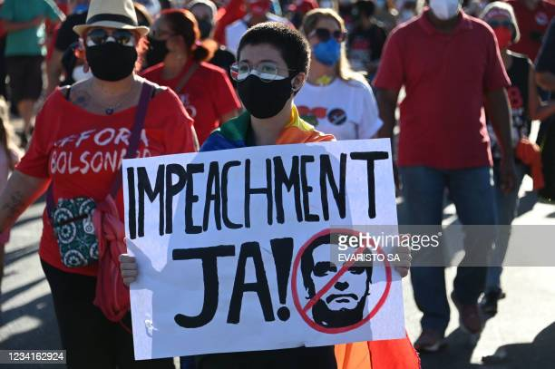 Demonstrator holds a sign reading Impeachment now! during a protest against the government of Brazilian President Jair Bolsonaro at the Esplanede of...