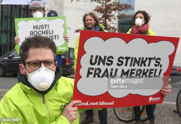 A demonstrator holds a sign reading 'It Stinks to Us Ms Merkel' outside a German federal parliament or Bundestag hearing on the Volkswagen emmissions...