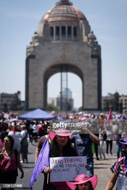 A demonstrator holds a sign reading Judas proved that not all who kiss love next to the Monumento a la Revolution during a rally on International...