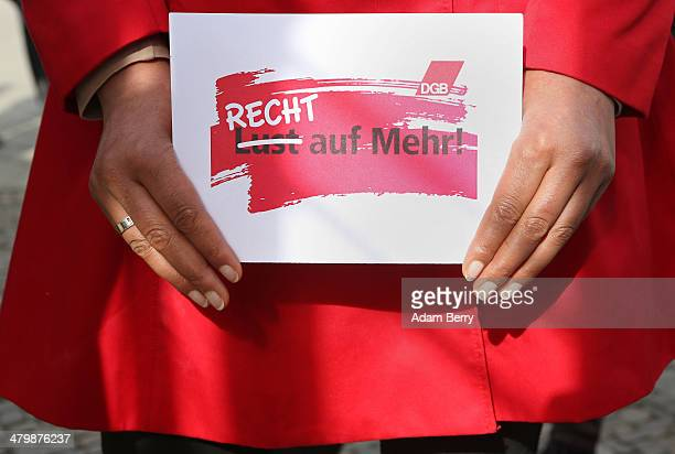 A demonstrator holds a sign reading 'Not a Wish But a Right to More' during the 'Equal Pay Day' demonstration on March 21 2014 in Berlin Germany The...