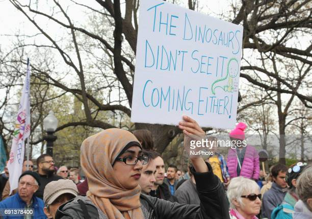 Demonstrator holds a sign saying 'the dinosaurs didn't see it coming either' as hundreds of Canadians took part in a massive march against climate...