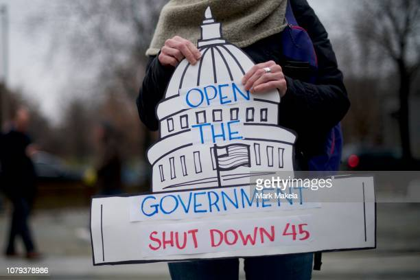 A demonstrator holds a sign shaped as the US Capitol building stating OPEN THE GOVERNMENT SHUT DOWN 45 as furloughed federal workers and area elected...