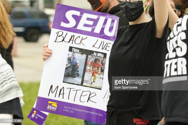 Demonstrator holds a sign showing former Minneapolis police officer Derek Chauvin and former NFL quarterback Colin Kaepernick during a peaceful...