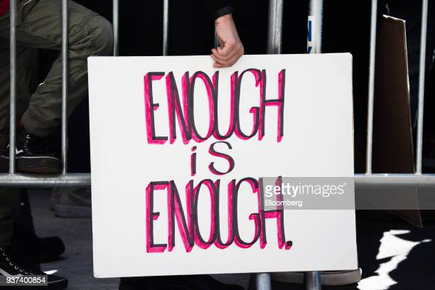 """Demonstrator holds a sign that reads """"Enough Is Enough,"""" while gathering on Central Park West during the March For Our Lives in New York, U.S., on..."""