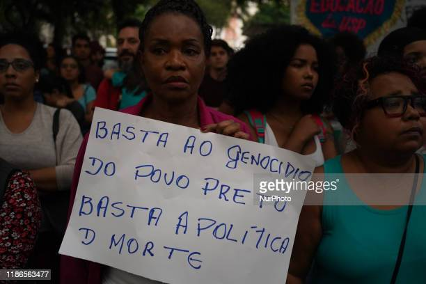 Demonstrator holds a sign that reads Enough of the genocide of the black people. Enough of the death policy. During a protest about the death of nine...