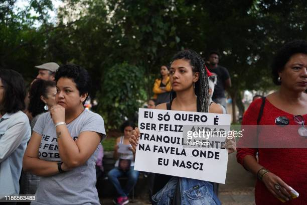 Demonstrator holds a sign that reads Eu só quero é ser feliz andar tranquilamente na favela onde eu nasci during a protest about the death of nine...