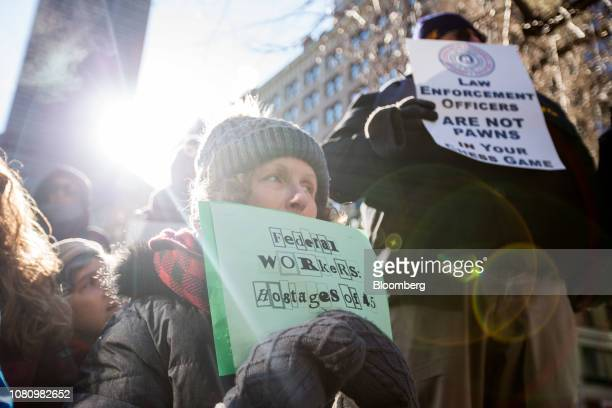 A demonstrator holds a sign that reads Federal Workers Hostages of 45 during a protest against the government shutdown in Boston Massachusetts US on...