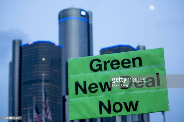 A demonstrator holds a sign that reads Green New Deal Now at a United Auto Workers candlelight vigil for General Motors Co workers at assembly plants...