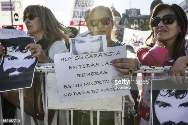 A demonstrator holds a sign that reads in Spanish 'Today His Face Is On All The Shirts He Is A Dead Man Who Continues To Be Born' during a 'Demand...
