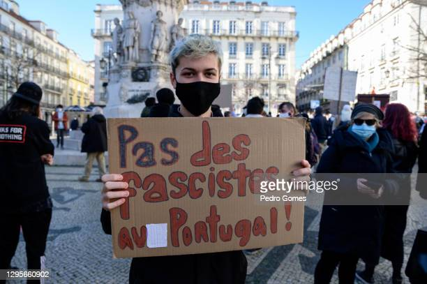 """Demonstrator holds a sign that reads """"No racists in Portugal"""" during a protest in Praça Camoes against the visit to Portugal of French far-right..."""