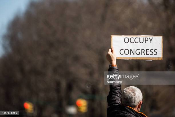 """Demonstrator holds a sign that reads """"Occupy Congress,"""" while gathering on Central Park West during the March For Our Lives in New York, U.S., on..."""