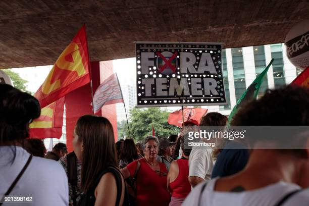 A demonstrator holds a sign that reads 'Out Temer' during a protest against pension reform in Sao Paulo Brazil on Monday Feb 19 2018 There may be a...