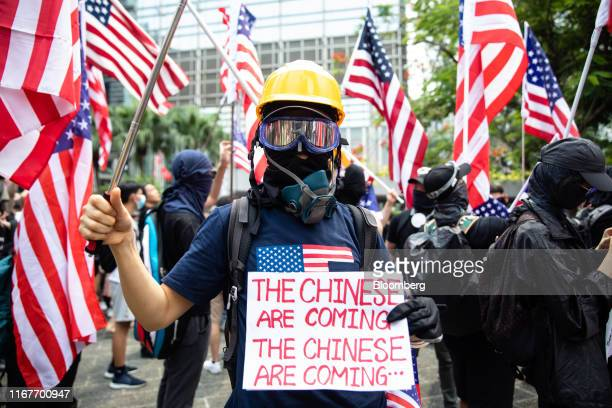 """Demonstrator holds a sign that reads """"The Chinese Are Coming"""" during a rally to petition the U.S. Congress to pass the """"Hong Kong Human Rights and..."""