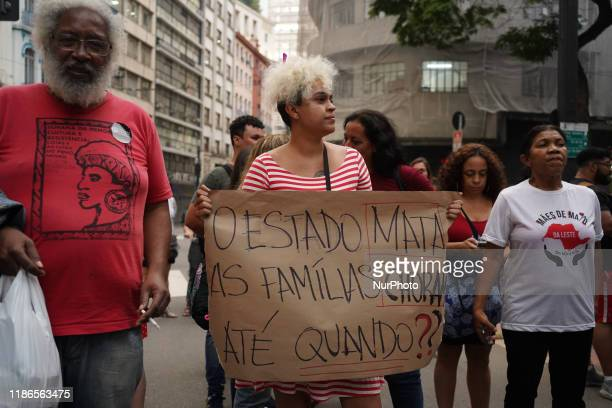 Demonstrator holds a sign that reads The State Kills. Families cry. Until when? during a protest about the death of nine people during a police raid...