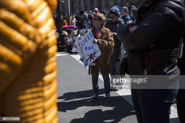 A demonstrator holds a sign that reads Vote 4 Lives Not Guns on Pennsylvania Avenue during the March For Our Lives in Washington DC US on Saturday...