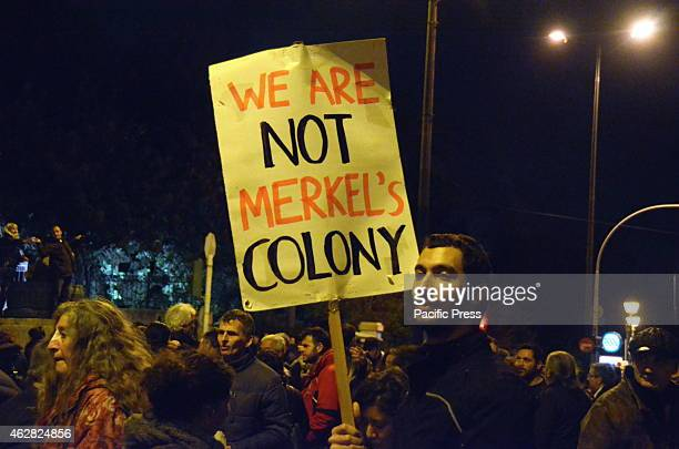 A demonstrator holds a sign that reads 'We are not Merkel's colony'A huge demonstration was organised in Syntagma square by Greek people to show...