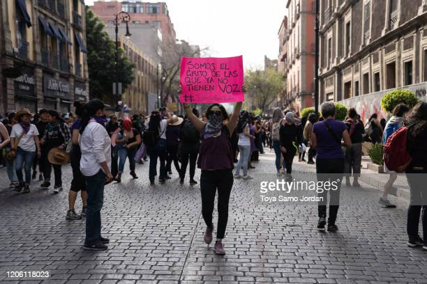 A demonstrator holds a sign that reads we are the scream of those who no longer have a voice during a rally on International Women's Day on March 8...