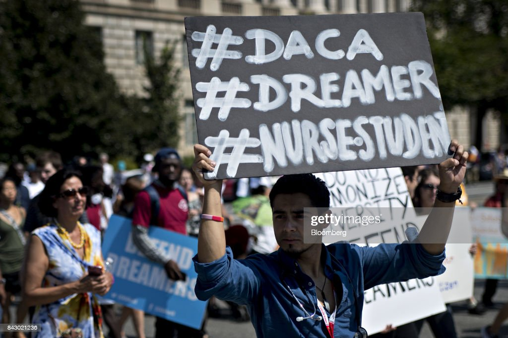 A demonstrator holds a sign while protesting the end of the Deferred Action for Childhood Arrivals (DACA) program in Washington, D.C., U.S., on Tuesday, Sept. 5, 2017. President Donald Trump will end an Obama-era program preventing the deportation of immigrants illegally brought to the U.S. as children, U.S. Attorney Jeff Sessions said today, putting in legal limbo about 1 million people who consider themselves Americans. Photographer: Andrew Harrer/Bloomberg via Getty Images