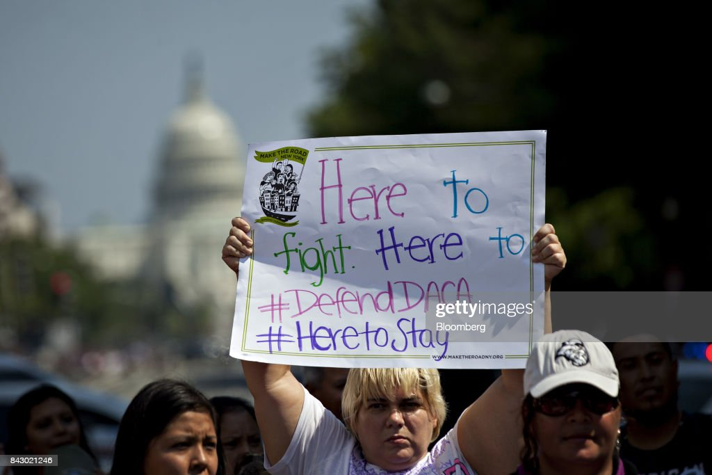 A demonstrator holds a sign while protesting the end of the Deferred Action for Childhood Arrivals (DACA) program outside Trump International Hotel in Washington, D.C., U.S., on Tuesday, Sept. 5, 2017. President Donald Trump will end an Obama-era program preventing the deportation of immigrants illegally brought to the U.S. as children, U.S. Attorney Jeff Sessions said today, putting in legal limbo about 1 million people who consider themselves Americans. Photographer: Andrew Harrer/Bloomberg via Getty Images