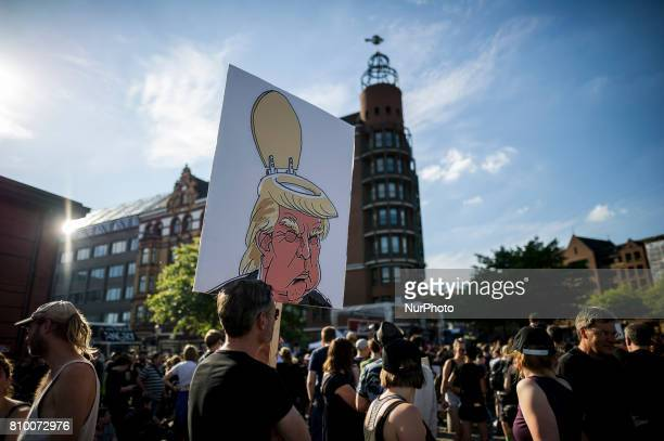 "Demonstrator holds a sign with a cartoon of Trump, in Hamburg, Germany, on July 6, 2017. The police stopped the left-radical demonstration ""G20..."