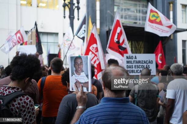 Demonstrator holds a sign with a photo one of the dead young boys and that reads Bruno Gabriel #justice during a protest about the death of nine...