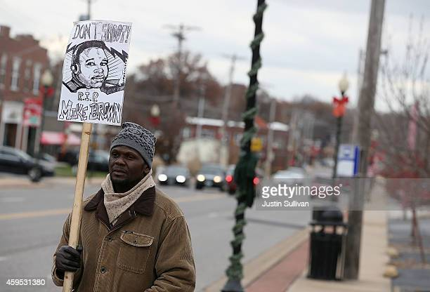A demonstrator holds a sign with an image of Michael Brown outside of the Ferguson police station on November 24 2014 in Ferguson Missouri A St Louis...