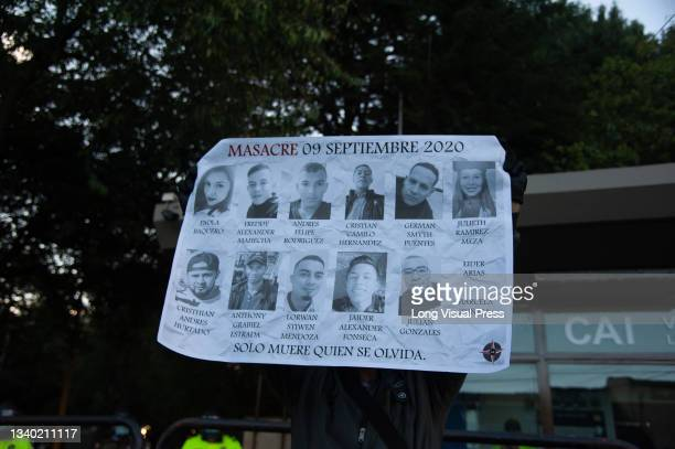 Demonstrator holds a sign with pictures of the 13 person who were killed during the violent unrest during the protests of the death of Javier Ordonez...