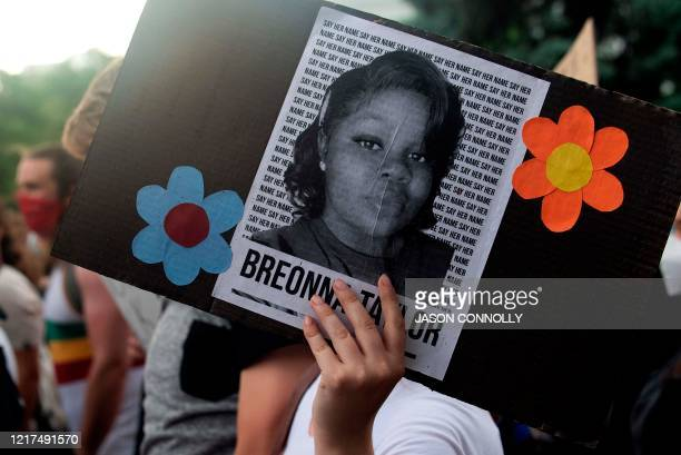 A demonstrator holds a sign with the image of Breonna Taylor a black woman who was fatally shot by Louisville Metro Police Department officers during...