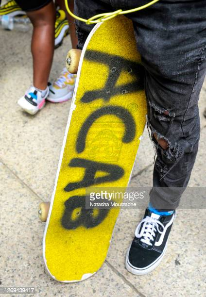 Demonstrator holds a skateboard with the letters ACAB sprayed on it during the Commitment March at the Lincoln Memorial on August 28, 2020 in...