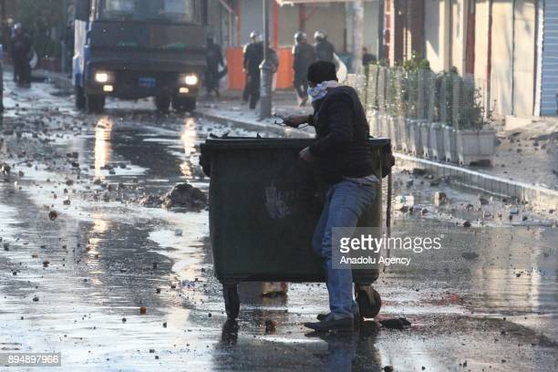 A demonstrator holds a slingshot as he ducks behind a trash bin while they clash with riot police within antigovernment protests in Sulaymaniyah Iraq...