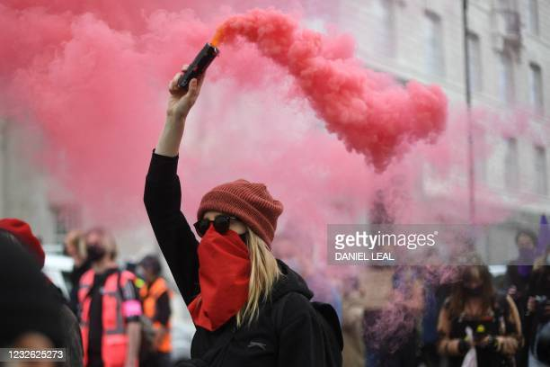Demonstrator holds a smoke bomb as she joins a protest against the Police, Crime, Sentencing and Courts Bill 2021 in central London on May 1, 2021. -...