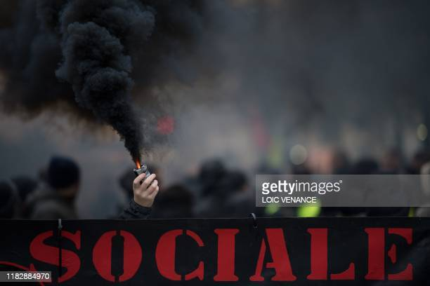 TOPSHOT A demonstrator holds a smoke generator during a demonstration marking the first anniversary of the yellow vest movement on November 16 in...
