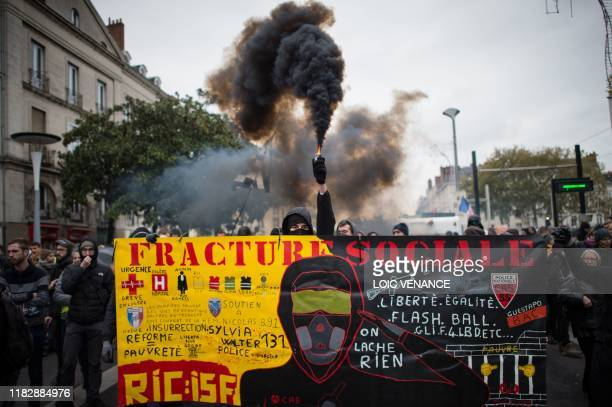 A demonstrator holds a smoke generator during a demonstration marking the first anniversary of the yellow vest movement on November 16 in Nantes...