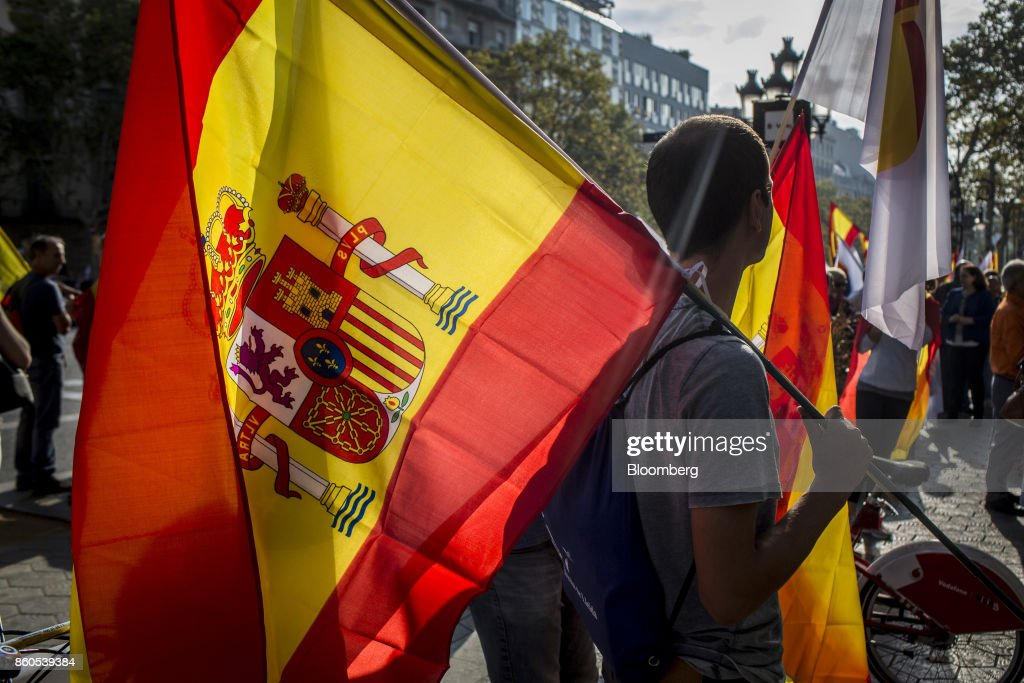A demonstrator holds a Spanish National flag in support of Spanish unity during a march on Spain's National Day in Barcelona, Spain, on Thursday, Oct. 12, 2017. Prime Minister Mariano Rajoy gave his Catalan antagonist Carles Puigdemont five days to clarify whether he has declared independence from Spain or not as the country prepared for its national holiday on Thursday. Photographer: Angel Garcia/Bloomberg via Getty Images