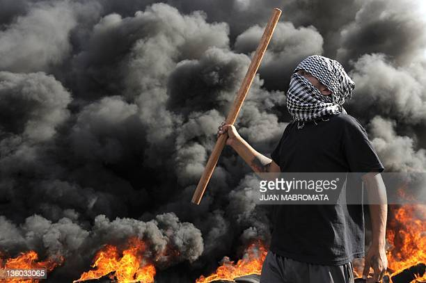 Demonstrator holds a stick next to burning tires blocking 9 de Julio Avenue in downtown Buenos Aires on December 20 during a protest for the 10th...