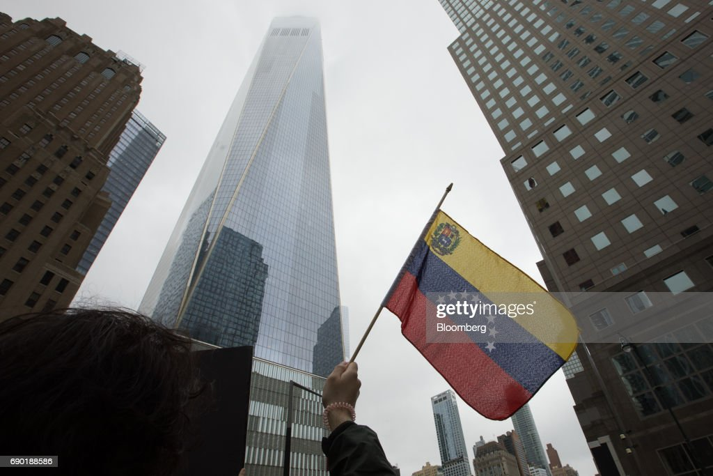 A demonstrator holds a Venezuelan flag during a protest outside of the Goldman Sachs Group Inc. headquarters in New York, U.S., on Tuesday, May 30, 2017. Goldman faces a probe by Venezuela's opposition leaders after buying bonds issued in 2014 by the state oil company, a purchase some lawmakers said bolsters PresidentNicolas Maduroas he grapples with accusations ofhuman-rights violations. Photographer: Alexander F. Yuan/Bloomberg via Getty Images