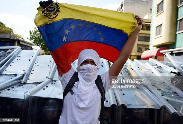 A demonstrator holds a Venezuelan flag in front of riot policemen during an opposition demo against the government of Venezuelan President Nicolas...