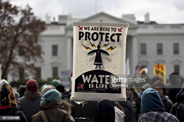 """Demonstrator holds a """"Water Is Life"""" sign in front of the White House during a protest against the Dakota Access Pipeline in Washington, D.C., U.S.,..."""