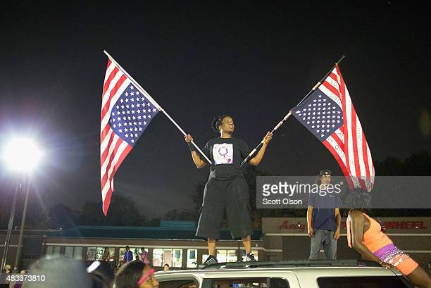A demonstrator holds American flags upside down as they protest in front of the police station to mark the first anniversary of the death of Michael...