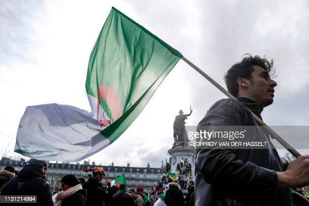 A demonstrator holds an Algerian flag during a protest over fears of plot to prolong the Algerian president's rule on Place de la Republique in Paris...