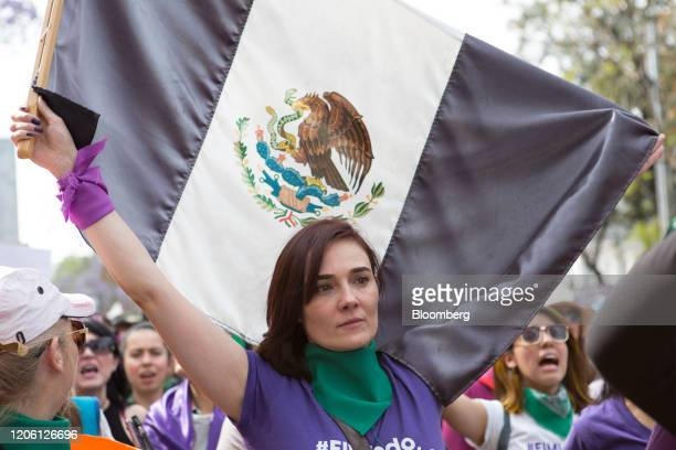 A demonstrator holds an altered version of the Mexican flag during a rally on International Women's Day in Mexico City Mexico on Friday March 8 2020...