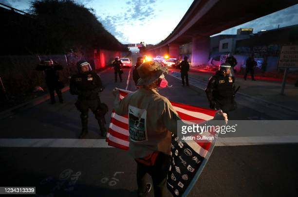 Demonstrator holds an American flag in front of California Highway Patrol officers during a protest sparked by the death of George Floyd while in...