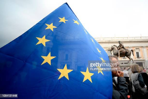 A demonstrator holds an EU flag in Rome 's Piazza del Campidoglio on October 27 2018 during a protest against the current decay of the capital under...