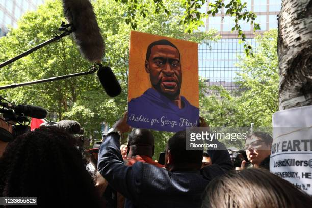 Demonstrator holds an image of George Floyd following the sentencing of former Minneapolis police office Derek Chauvin outside Hennepin County...
