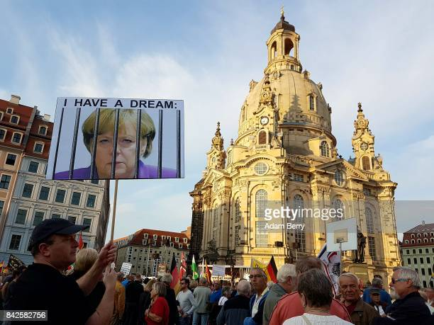 A demonstrator holds an image of German Chancellor Angela Merkel behind prison bars at a Pegida demonstration on September 4 2017 in Dresden Germany...