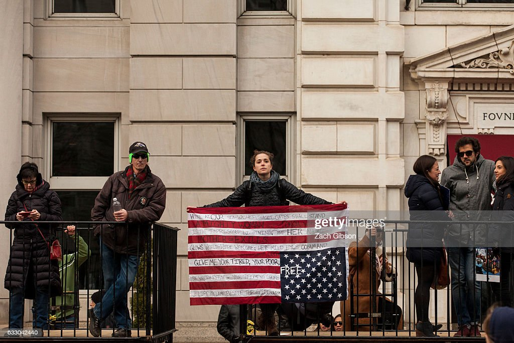A demonstrator holds an inverted American flag during a protest on January 29, 2017 in Washington, DC. Protestors in Washington and around the country gathered to protest President Donald Trump's executive order barring the citizens of Muslim-majority countries Iraq, Syria, Iran, Sudan, Libya, Somalia and Yemen from traveling to the United States.